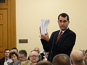 Kansas Attorney General Derek Schmidt holds up the volumes of court opinions that have been written in the ongoing school finance lawsuit, Gannon v. Kansas, while urging state lawmakers to consider a constitutional amendment that would clarify the state's role in funding public schools.
