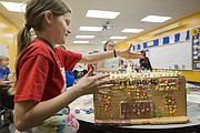 Sunflower Elementary fifth-grader Zoey Miller adds sprinkles to a snowman on the roof of a gingerbread likeness of Allen Fieldhouse on Wednesday, Dec. 20, 2017 at the school. Several classes at the school participated in constructing gingerbread representations of Lawrence's iconic buildings and landmarks, which they shared digitally with pen pals in Lithuania.