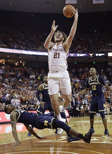 Texas forward Dylan Osetkowski (21) drives to the basket over Michigan guard Charles Matthews (1) during the second half of an NCAA college basketball game, Tuesday, Dec. 12, 2017, in Austin, Texas. Michigan won 59-52.