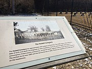 A plaque outside the Haskell Indian Nations University cemetery, seen here, commemorates the 103 Native American children buried there between 1885 and 1943. The university recently installed a newer, taller fence around the cemetery in an effort to protect the graveyard from vandals.