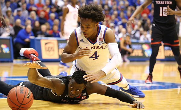 Kansas guard Devonte' Graham (4) and Texas Tech center Norense Odiase (32) dive for a ball during the first half, Tuesday, Jan. 2, 2018 at Allen Fieldhouse.