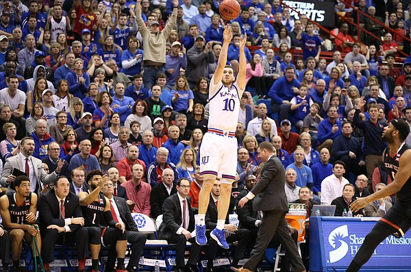 Kansas guard Sviatoslav Mykhailiuk (10) puts up a three before the Texas Tech bench during the first half, Tuesday, Jan. 2, 2018 at Allen Fieldhouse.
