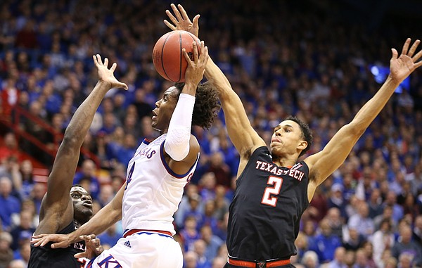 Kansas guard Devonte' Graham (4) is defended by Texas Tech center Norense Odiase, left, and Texas Tech guard Zhaire Smith (2) during the first half, Tuesday, Jan. 2, 2018 at Allen Fieldhouse.