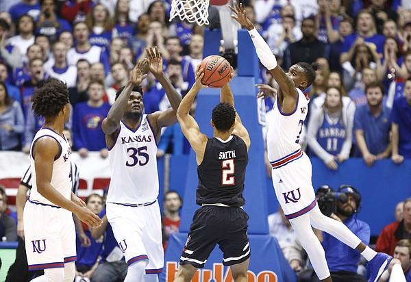 Kansas center Udoka Azubuike (35) and Kansas guard Lagerald Vick (2) come in to defend against a three from Texas Tech guard Zhaire Smith (2) during the second half, Tuesday, Jan. 2, 2018 at Allen Fieldhouse.