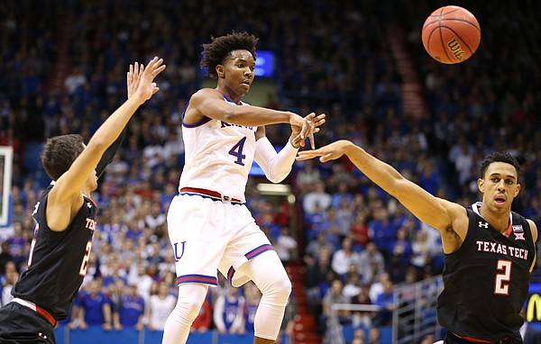 Kansas guard Devonte' Graham (4) throws a pass to the wing while defended by Texas Tech guard Davide Moretti, left, and Texas Tech guard Zhaire Smith (2) during the second half, Tuesday, Jan. 2, 2018 at Allen Fieldhouse.