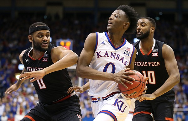 Kansas guard Marcus Garrett (0) moves to the bucket between Texas Tech forward Tommy Hamilton IV (0) and Texas Tech guard Niem Stevenson (10) during the second half, Tuesday, Jan. 2, 2018 at Allen Fieldhouse.
