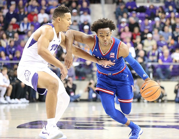 Kansas guard Devonte' Graham (4) drives against TCU guard Desmond Bane (1) during the second half, Saturday, Jan. 6, 2018 at Schollmaier Arena.
