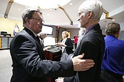 Outgoing Lawrence City Commissioner Mike Amyx greets Kansas State Rep. Boog Highberger, D-Lawrence, during a recess in the City Commission meeting on Monday, Jan. 8, 2018 at City Hall.