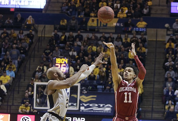 Oklahoma guard Trae Young (11) shoots while being defended by West Virginia guard Jevon Carter (2) during the first half of an NCAA college basketball game Saturday, Jan. 6, 2018, in Morgantown, W.Va. (AP Photo/Raymond Thompson)