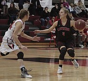 Lawrence High's Leslie Ostronic surveys the court during the second half of the Lions' 62-30 win over Shawnee Mission North on Friday.