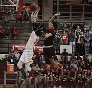 Lawrence High's Van Dave Jacob goes up for a block against Shawnee Mission North's Tommy Faseru in the first half of the Lions' 72-64 win over the Indians on Friday.