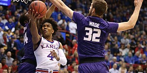 Kansas guard Devonte' Graham (4) gets to the bucket under Kansas State forward Dean Wade (32) and Kansas State forward Makol Mawien (14) during the first half, Saturday, Jan. 13, 2018 at Allen Fieldhouse.