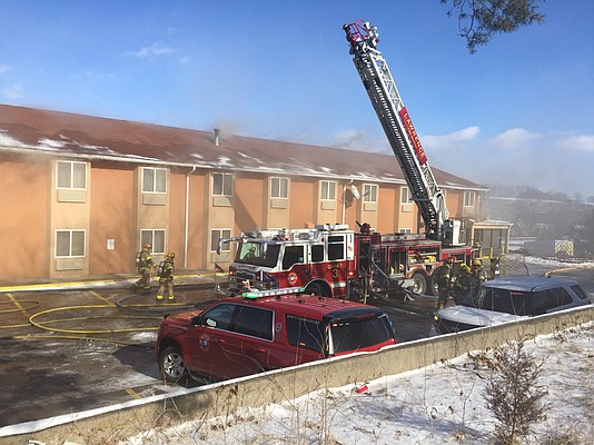 Smoke pours from America's Best Value Inn, 515 McDonald Drive, as firefighters move equipment into position, Monday, Jan. 15, 2018.