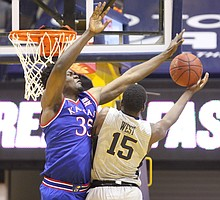 Kansas center Udoka Azubuike (35) defends against a shot from West Virginia forward Lamont West (15) during the first half, Monday, Jan. 15, 2018 at WVU Coliseum in Morgantown, West Virginia.