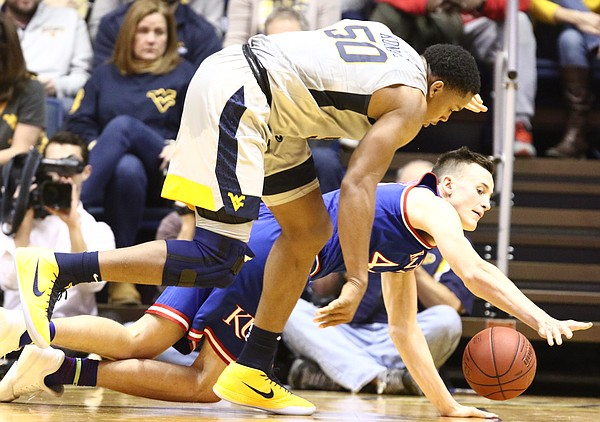 Kansas forward Mitch Lightfoot (44) lays out to try to grab a loose ball with West Virginia forward Sagaba Konate (50) during the first half, Monday, Jan. 15, 2018 at WVU Coliseum in Morgantown, West Virginia.