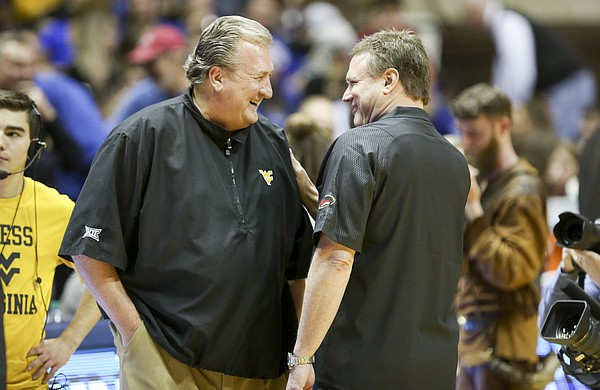 Kansas head coach Bill Self and West Virginia head coach Bob Huggins have a laugh before tipoff on Monday, Jan. 15, 2018 at WVU Coliseum in Morgantown, West Virginia. Self sported a Huggins-style pullover given to him by Huggins before the game.