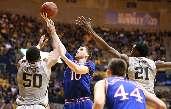 Kansas guard Sviatoslav Mykhailiuk (10) floats in for a shot against West Virginia forward Sagaba Konate (50) and West Virginia forward Wesley Harris (21) during the first half, Monday, Jan. 15, 2018 at WVU Coliseum in Morgantown, West Virginia.