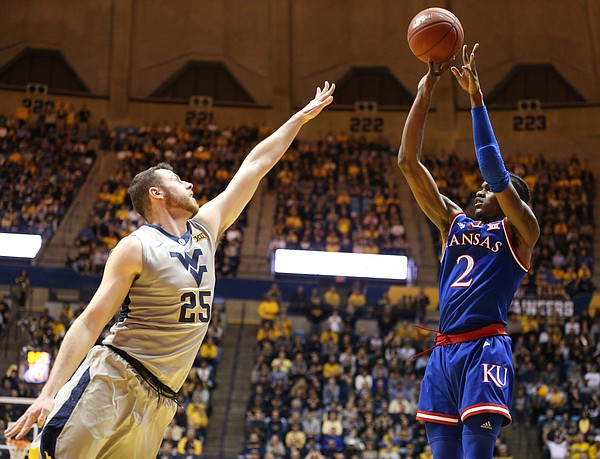 Kansas guard Lagerald Vick (2) puts up a three over West Virginia forward Maciej Bender (25) during the first half, Monday, Jan. 15, 2018 at WVU Coliseum in Morgantown, West Virginia.