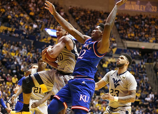 West Virginia forward Sagaba Konate (50) rips a rebound away from Kansas forward Silvio De Sousa (22) during the first half, Monday, Jan. 15, 2018 at WVU Coliseum in Morgantown, West Virginia. At right is West Virginia forward Esa Ahmad (23).