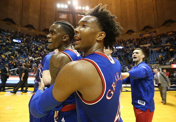 Kansas guard Devonte' Graham (4) grabs Kansas guard Lagerald Vick (2) as the Jayhawks celebrate their 71-66 win over West Virginia, Monday, Jan. 15, 2018 at WVU Coliseum in Morgantown, West Virginia.