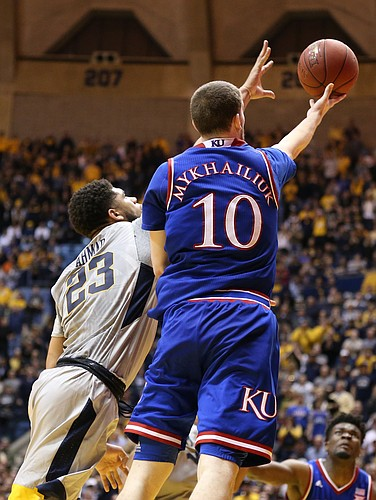 Kansas guard Sviatoslav Mykhailiuk (10) scoops in a bucket past West Virginia forward Esa Ahmad (23) during the second half, Monday, Jan. 15, 2018 at WVU Coliseum in Morgantown, West Virginia.