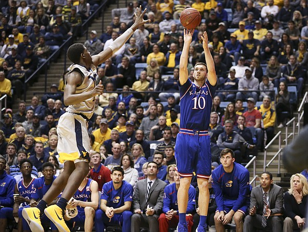 Kansas guard Sviatoslav Mykhailiuk (10) puts up a three from the corner against West Virginia forward Lamont West (15) during the second half, Monday, Jan. 15, 2018 at WVU Coliseum in Morgantown, West Virginia.
