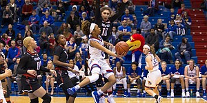 Kansas guard Christalah Lyons (0) attempts to finish a layup around Texas Tech's Grayson Bright on Wednesday at Allen Fieldhouse.