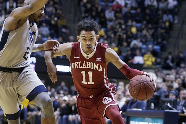 Oklahoma guard Trae Young (11) drives while being defended by West Virginia guard Jevon Carter (2) during the first half of an NCAA college basketball game,0 Saturday, Jan. 6, 2018, in Morgantown, W.Va.