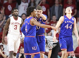 Kansas guard Sviatoslav Mykhailiuk (10) and Kansas guard Devonte' Graham (4) come together for a talk during the first half at Lloyd Noble Center on Tuesday, Jan. 23, 2018 in Norman, Oklahoma.