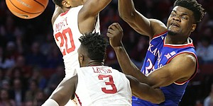 Kansas center Udoka Azubuike (35) dumps a pass to the middle beyond Oklahoma guard Kameron McGusty (20) and Oklahoma forward Khadeem Lattin (3) during the first half at Lloyd Noble Center on Tuesday, Jan. 23, 2018 in Norman, Oklahoma.