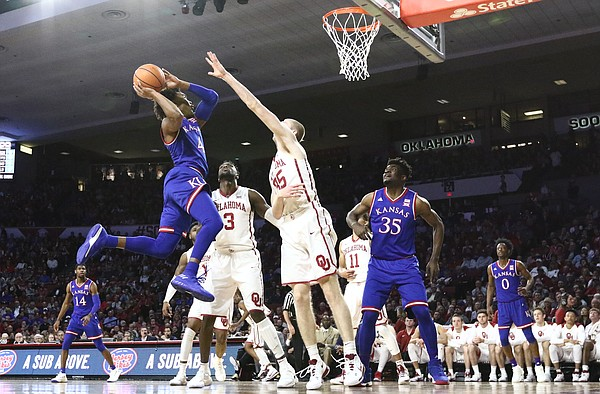 Kansas guard Devonte' Graham (4) comes in for a shot against Oklahoma forward Brady Manek (35) during the first half at Lloyd Noble Center on Tuesday, Jan. 23, 2018 in Norman, Oklahoma.