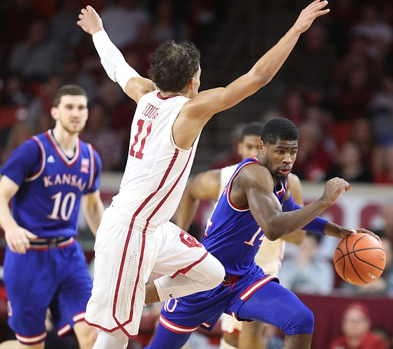 Kansas guard Malik Newman (14) tries to drive against Oklahoma guard Trae Young (11) during the second half at Lloyd Noble Center on Tuesday, Jan. 23, 2018 in Norman, Oklahoma.