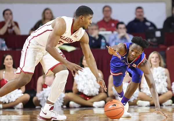 Kansas guard Marcus Garrett (0) can't quite get to a loose ball as it is scooped up by Oklahoma guard Christian James (0) during the second half at Lloyd Noble Center on Tuesday, Jan. 23, 2018 in Norman, Oklahoma.