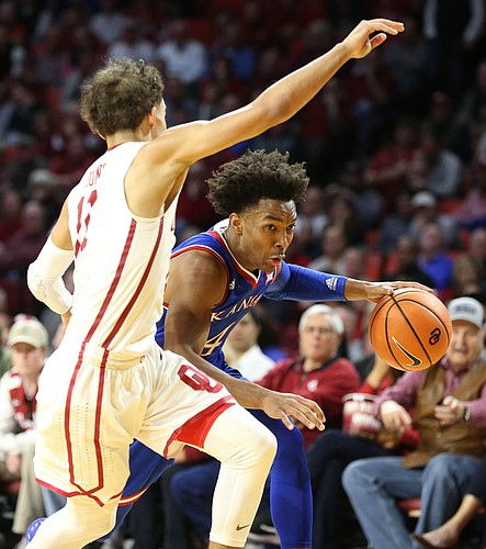 Kansas guard Devonte' Graham (4) drives against Oklahoma guard Trae Young (11) during the second half at Lloyd Noble Center on Tuesday, Jan. 23, 2018 in Norman, Oklahoma.