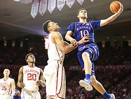 Kansas guard Sviatoslav Mykhailiuk (10) puts a shot past Oklahoma center Jamuni McNeace (4) during the second half at Lloyd Noble Center on Tuesday, Jan. 23, 2018 in Norman, Oklahoma.