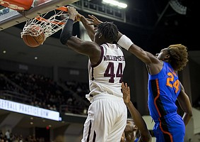 Texas A&M forward Robert Williams (44) dunks the ball as Florida guard Deaundrae Ballard (24) defends during the first half of an NCAA college basketball game Tuesday, Jan. 2, 2018, in College Station, Texas.