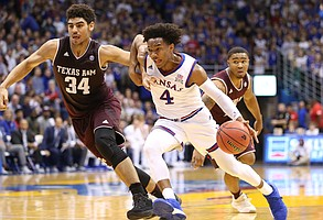 Kansas guard Devonte' Graham (4) tries to shrug off Texas A&M center Tyler Davis (34) on his way to the bucket during the first half, Saturday, Jan. 27, 2018 at Allen Fieldhouse.