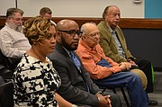 Anthony Lewis, second from left, and his wife Tiffany Lewis, far left, listen to a speaker at the Lawrence school board meeting on Monday, Jan. 29, 2018 at the USD 497 district headquarters. Anthony Lewis was approved as the district's next superintendent at the meeting.