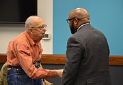 Austin Turney, a former Lawrence school board member, shakes hands with Anthony Lewis, the newly approved district superintendent, at the board meeting Monday, Jan. 29, 2018 at district offices, 110 McDonald Drive.