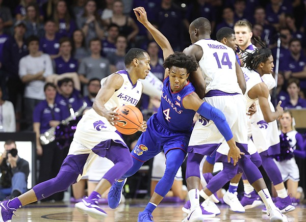 Kansas guard Devonte' Graham (4) rolls through a pick as he defends Kansas State guard Barry Brown (5) during the first half, Monday, Jan. 29, 2018 at Bramlage Coliseum in Manhattan, Kan.