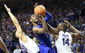 Kansas guard Malik Newman (14) gets a shot off as he is fouled by Kansas State forward Makol Mawien (14) during the second half, Monday, Jan. 29, 2018 at Bramlage Coliseum in Manhattan, Kan. At left is Kansas State guard Mike McGuirl (00).