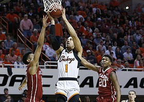 Oklahoma State guard Kendall Smith (1) shoots between Oklahoma guard Jordan Shepherd, left, and guard Kameron McGusty (20) in the first half of an NCAA college basketball game in Stillwater, Okla., Saturday, Jan. 20, 2018.