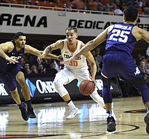 Oklahoma State guard Jeffrey Carroll, center, drives the ball between TCU guards Kenrich Williams, left, and Alex Robinson in the first half of a NCAA college basketball game in Stillwater, Okla., Tuesday, Jan. 30, 2018.