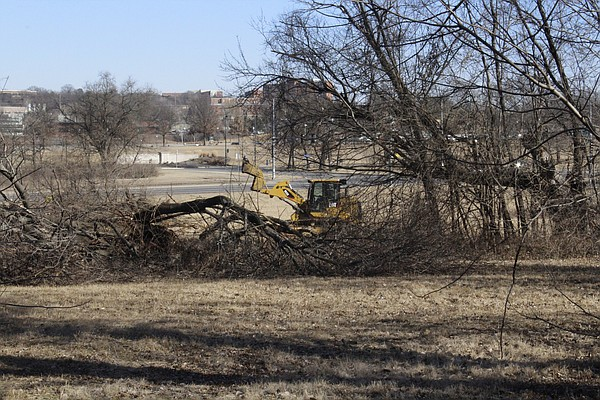 A bulldozer clears trees Friday morning on property near the southwest corner of Clinton Parkway and Crestline Drive.