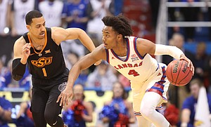 Kansas guard Devonte' Graham (4) takes off with the ball after picking off a pass to Oklahoma State guard Kendall Smith (1) during the first half, Saturday, Feb. 3, 2018 at Allen Fieldhouse.