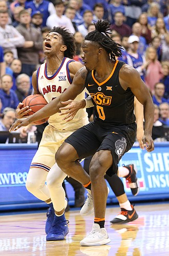 Kansas guard Devonte' Graham (4) is fouled by Oklahoma State guard Brandon Averette (0) during the second half, Saturday, Feb. 3, 2018 at Allen Fieldhouse.
