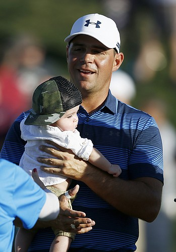 After his one-hole playoff win, Gary Woodland holds his son Jaxson on the 18th green after the final round of the Waste Management Phoenix Open golf tournament Sunday, Feb. 4, 2018, in Scottsdale, Ariz. (AP Photo/Ross D. Franklin)