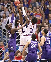 Kansas guard Malik Newman (14) and Kansas guard Lagerald Vick (2) fight for a rebound with TCU forward Kouat Noi (12) during the first half on Tuesday, Feb. 6, 2018 at Allen Fieldhouse.