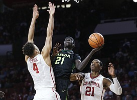 Baylor forward Nuni Omot (21) drives to the basket between Oklahoma center Jamuni McNeace (4) and forward Kristian Doolittle (21) during the first half of an NCAA college basketball game in Norman, Okla., Tuesday, Jan. 30, 2018.