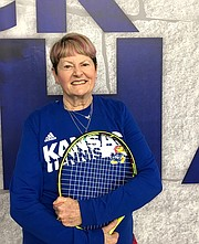 Ann Anderson, coach of the senior tennis class at the Jayhawk Tennis Center, poses with her racket on Feb. 2, 2018, at JTC, 233 Rock Chalk Lane. She has been playing tennis since she was 4 years old.